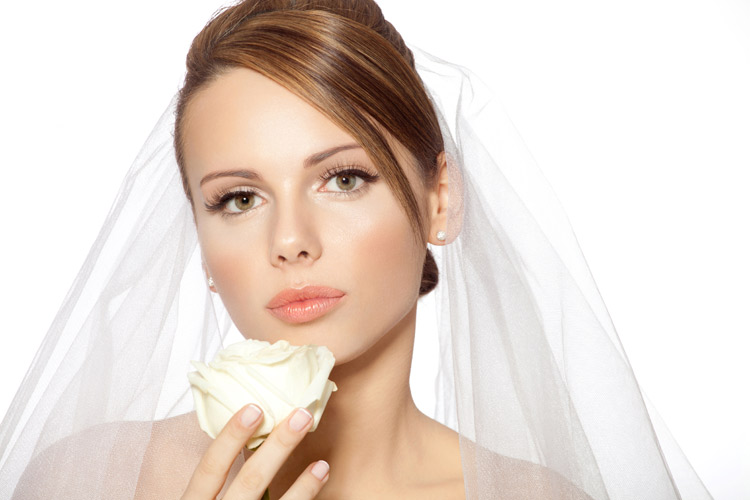 bruid ruikt roos met sluier om en parel oorbellen in